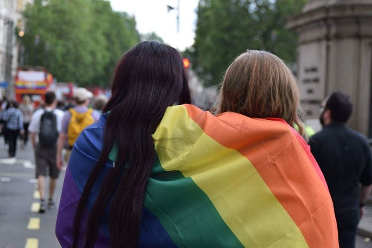 2 lady wrapped up in a pride flag