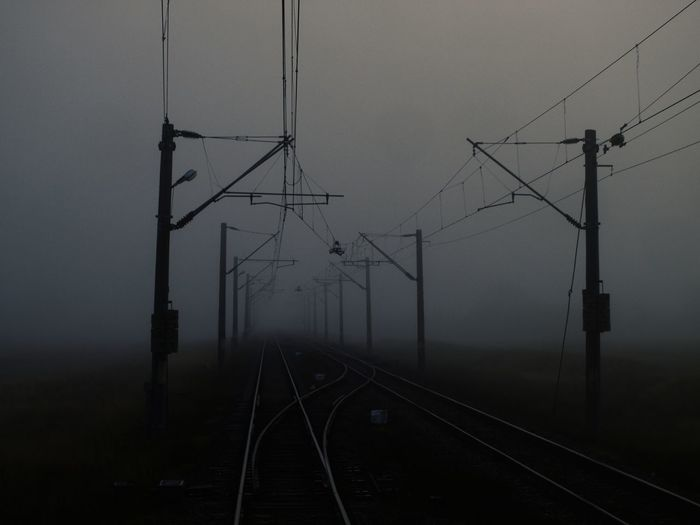 Diminishing perspective of railroad track against sky during foggy weather