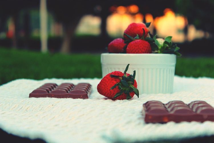 Close-up of chocolate and strawberries with bowl on white fabric at park