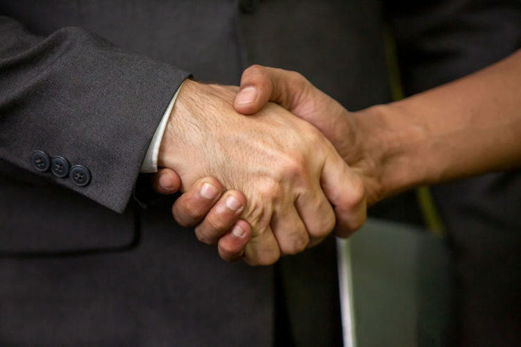 Midsection of man shaking hand with colleague