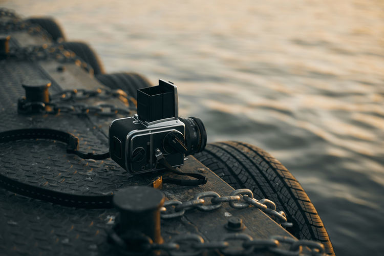 Close-up of camera against sea during sunset