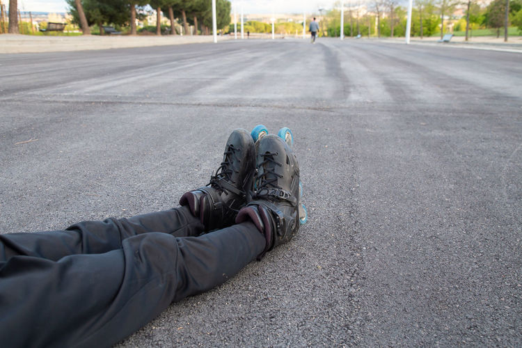 Low section of man relaxing on road