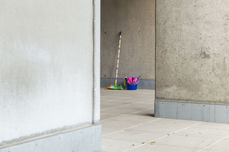 Multi Colored Broom With Bucket On Floor Against Wall Seen From Doorway