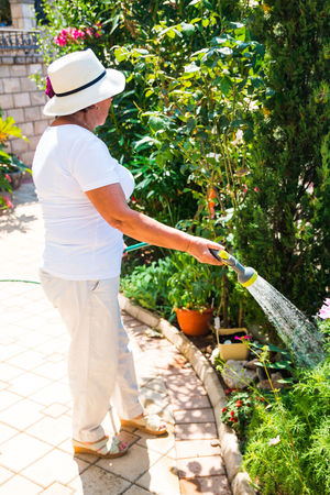 Casual Clothing Day Full Length Gardening Growth Hat Leisure Activity Lifestyles Nature One Person Outdoors People Plant Real People Rear View Standing Sun Hat Sunlight Tree Women
