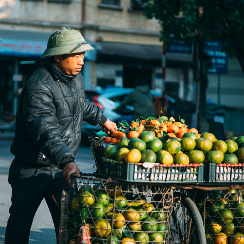 Male street vendor with fruits on bicycle in city