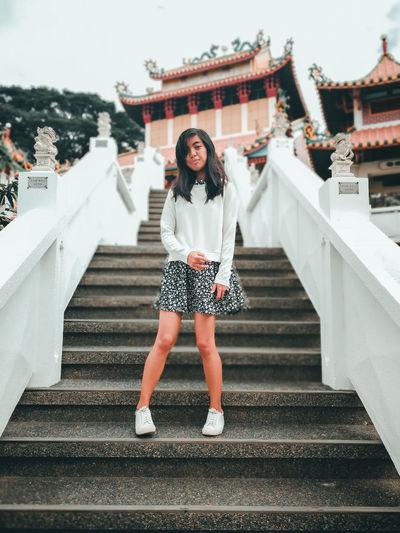 Full length portrait of teenage girl standing on steps