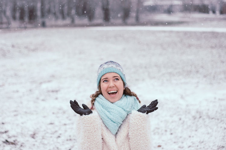 Smiling young woman standing at park during snowing