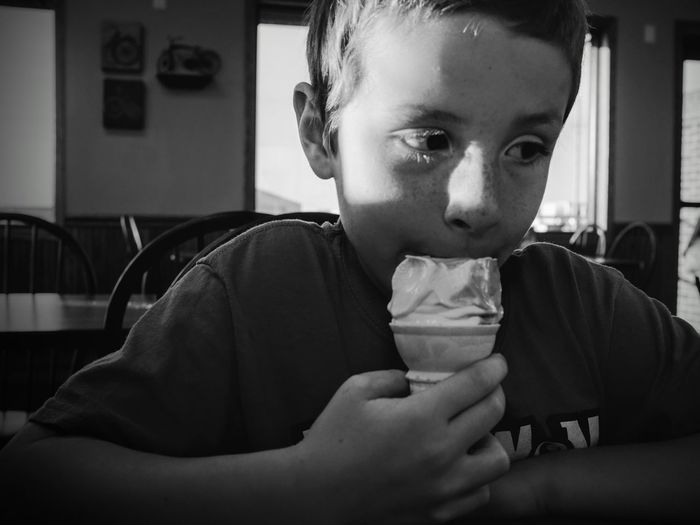 Boy eating ice cream in restaurant