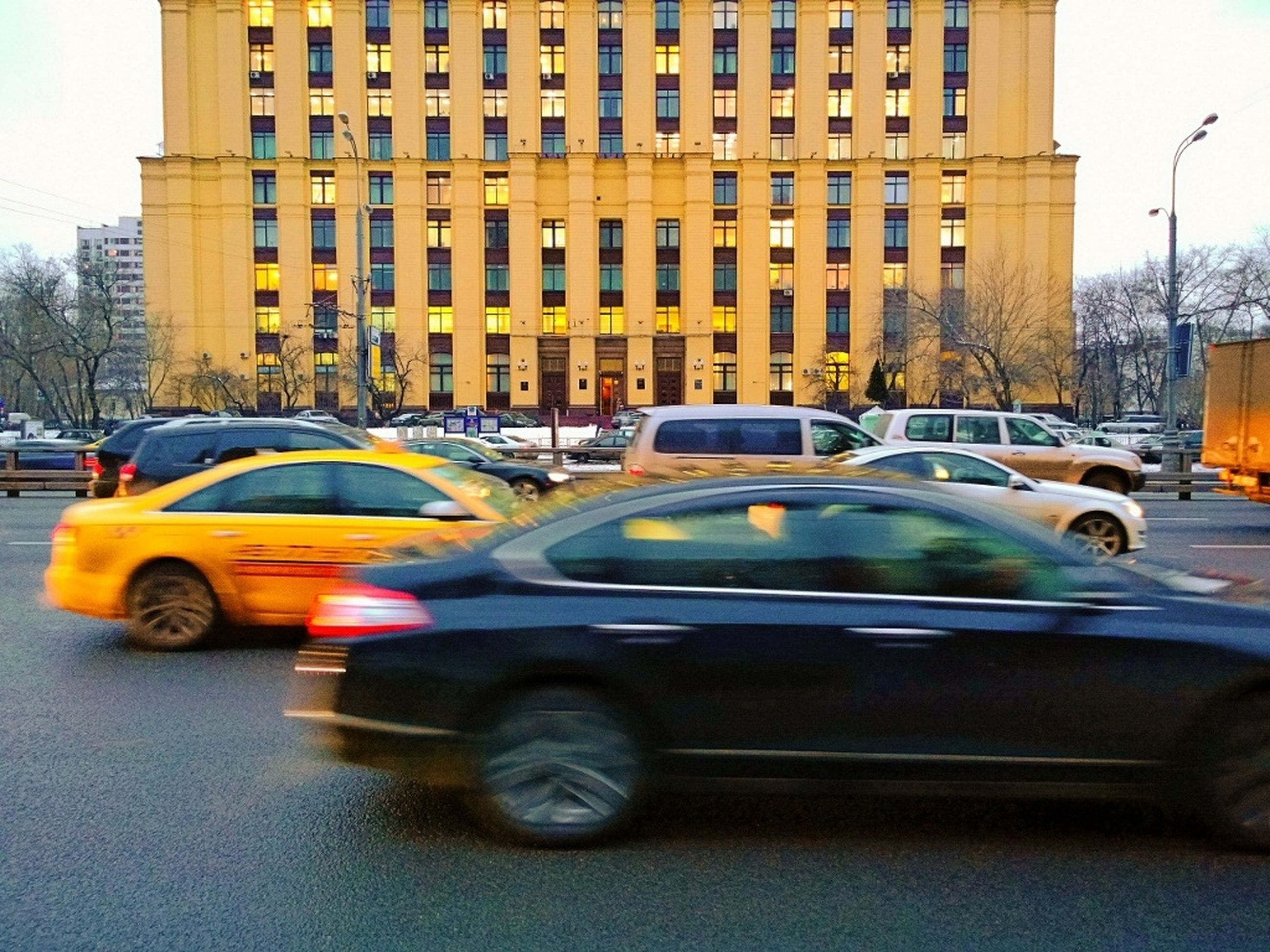 transportation, land vehicle, car, mode of transport, architecture, building exterior, built structure, city, street, road, city street, travel, traffic, city life, on the move, headlight, building, vehicle, stationary, bus