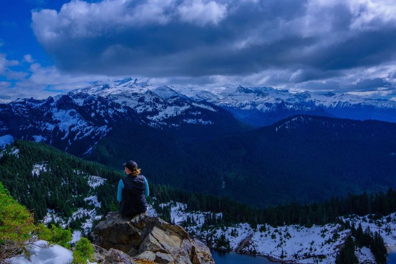 Rear view of hiker sitting on rock against snowcapped mountain