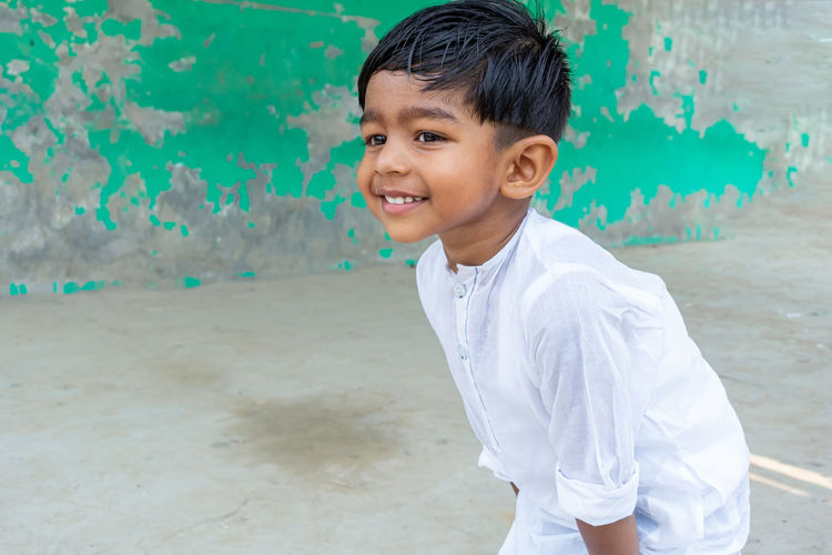 Cute smiling boy standing outdoors