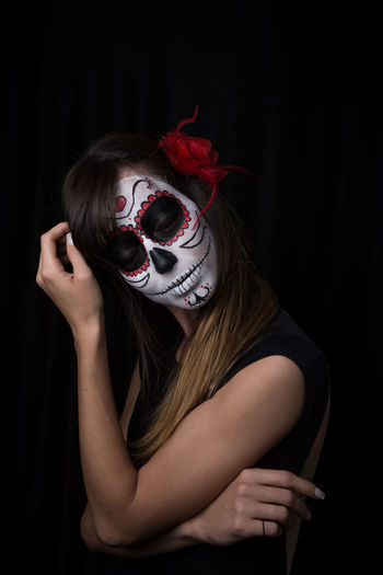 Midsection of woman wearing mask against black background