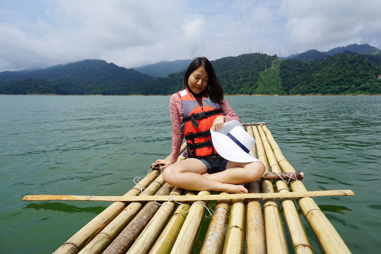 Smiling Young Woman Sitting On Wooden Raft Amidst Lake Against Sky