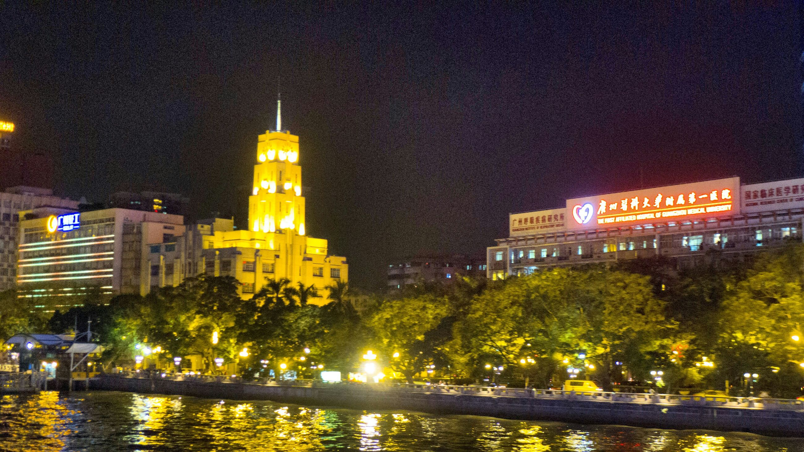 architecture, building exterior, built structure, illuminated, night, city, water, tower, reflection, waterfront, tall - high, travel destinations, river, sky, skyscraper, city life, famous place, tree, capital cities, clock tower
