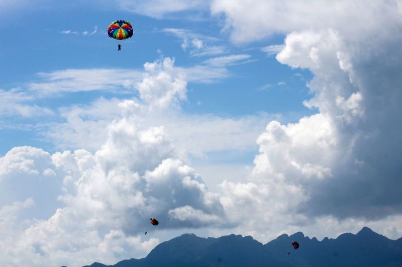 Adventure Beauty In Nature Cloud Cloud - Sky Cloudy Day Extreme Sports Flying Freedom Hot Air Balloon Leisure Activity Lifestyles Low Angle View Mid-air Mountain Mountain Range Nature Outdoors Parachute Paragliding Scenics Sky Tranquil Scene Tranquility Unrecognizable Person