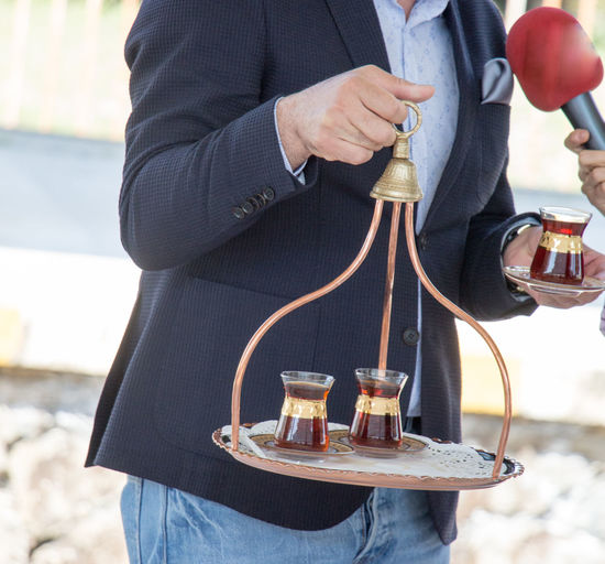 Midsection Of Man Serving Turkish Tea