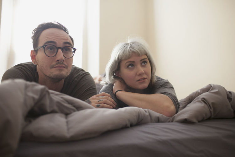 Portrait of young man and woman lying on bed