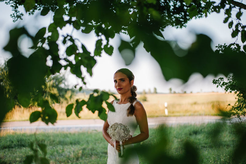 Portrait of bride with bouquet standing by tree on field