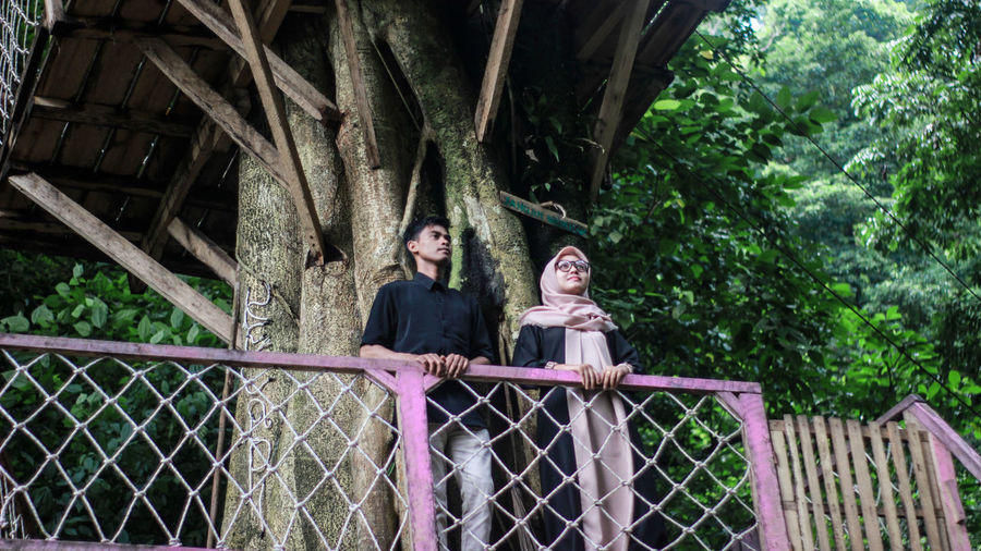 Man and woman on footbridge against trees in forest