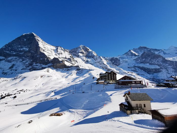 Scenic view of houses against mountains and clear blue sky