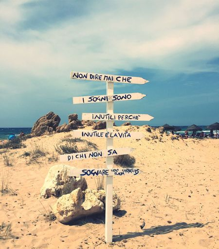 Text Western Script Communication Guidance Sand Cloud - Sky Sky Beach Day Outdoors Direction Nature Sea Tranquility Scenics No People Road Sign Water Beauty In Nature Horizon Over Water