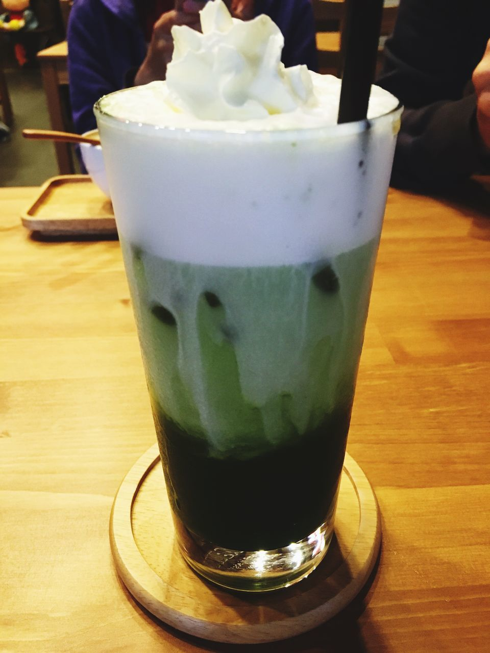 food and drink, table, drink, freshness, drinking glass, refreshment, serving size, indoors, food, close-up, restaurant, incidental people, green color, indulgence, temptation, sweet food, unhealthy eating, frothy drink, ready-to-eat, real people, dessert, cold temperature, matcha tea, day