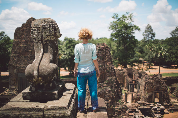 Cambodia Siem Reap Angkor Architecture Casual Clothing Creativity Curly Hair Day Full Length Girl Hairstyle Leisure Activity Lifestyles Nature One Person Outdoors Plant Real People Rear View Representation Sky Standing Sunlight Tree My Best Travel Photo