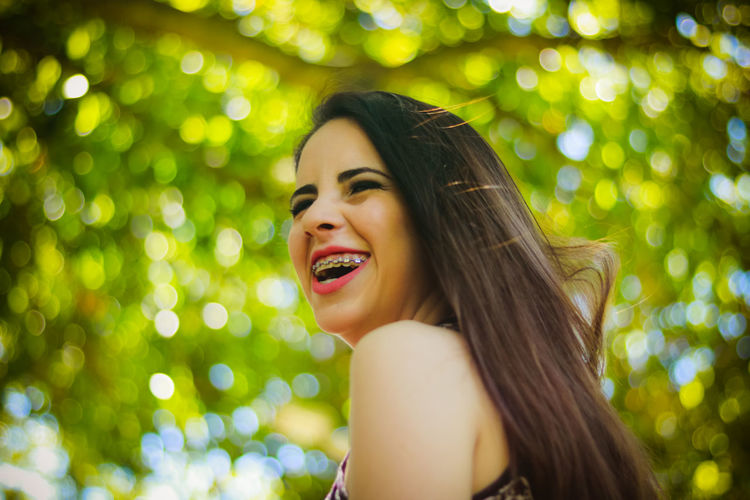 Close-up of happy young woman against tree