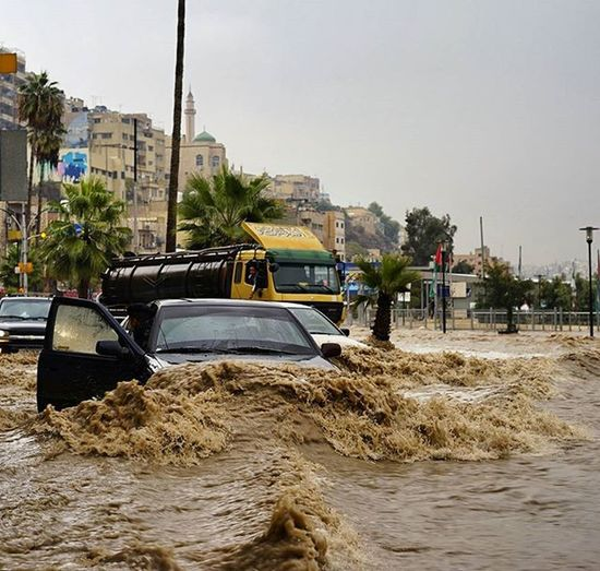 Cars flooded and getting carried down the street in downtown Amman during a flash flood Jordan