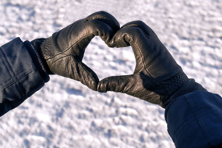 Male hands in black gloves are folded in shape of heart against background of white snow