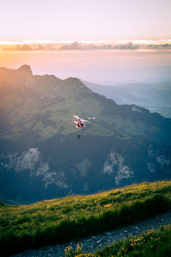 Helicopter Flying Over Landscape Against Sky