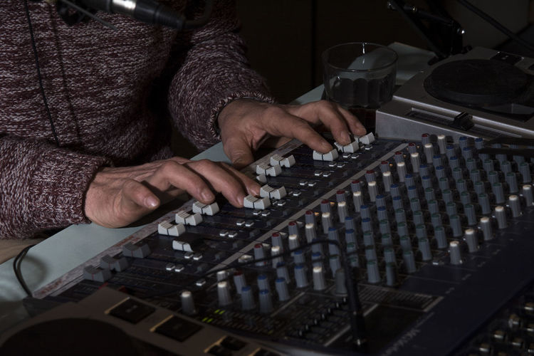 Midsection of dj playing sound mixer