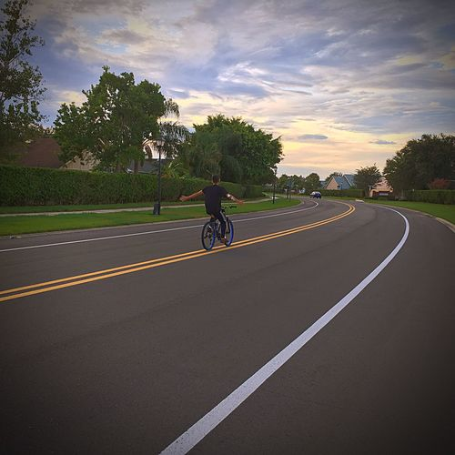 The open road Transportation Road Land Vehicle Mode Of Transport Sky Cycling The Way Forward Full Length Tree Road Marking On The Road On The Move Clouds And Sky Motion Diminishing Perspective Diminishing Point Vanishing Point Outdoors Country Road Day Sunset Grass Neighborhood in Orlando with TM Productions