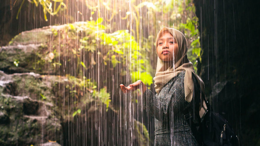 Young woman wearing hijab standing by waterfall