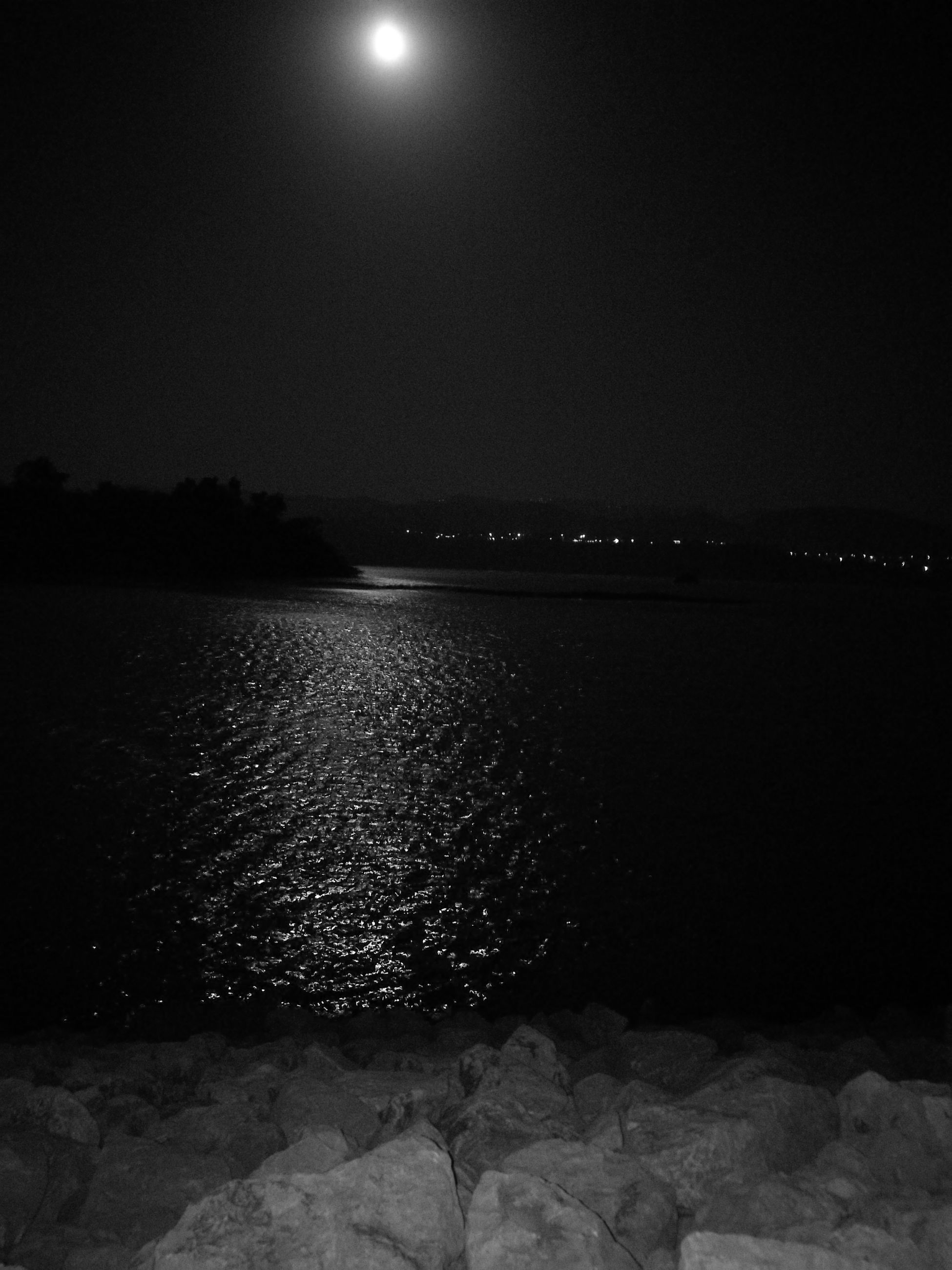moon, night, water, tranquil scene, scenics, tranquility, glowing, nature, sea, non-urban scene, beauty in nature, shore, outdoors, seascape, sky, riverbank, calm, distant, moonlight, no people, remote, vacations, majestic