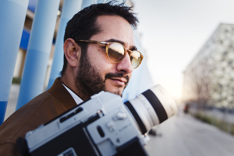 Close-up of man wearing sunglasses holding camera