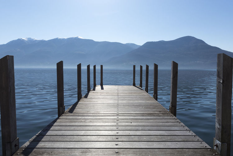 Pier on an alpine lake Maggiore with mountain in a sunny day in Ticino, Switzerland. Alpine Lakes Wilderness Beauty In Nature Blue Sky Built Structure Clear Sky Day Diminishing Perspective Jetty Lake Lake Maggiore Mountain Mountain Range Nature No People Outdoors Pier Scenics Sunlight Swiss Alps Tranquil Scene Tranquility Vanishing Point Water Wood - Material Wood Paneling