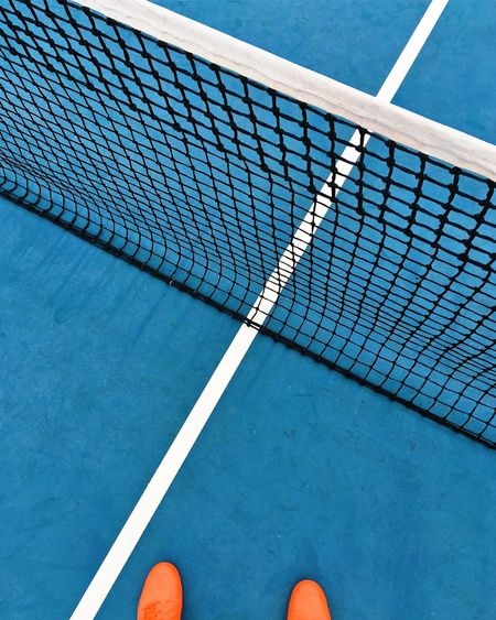 Low section of person standing on tennis court