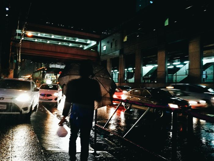 Man standing on wet street at night
