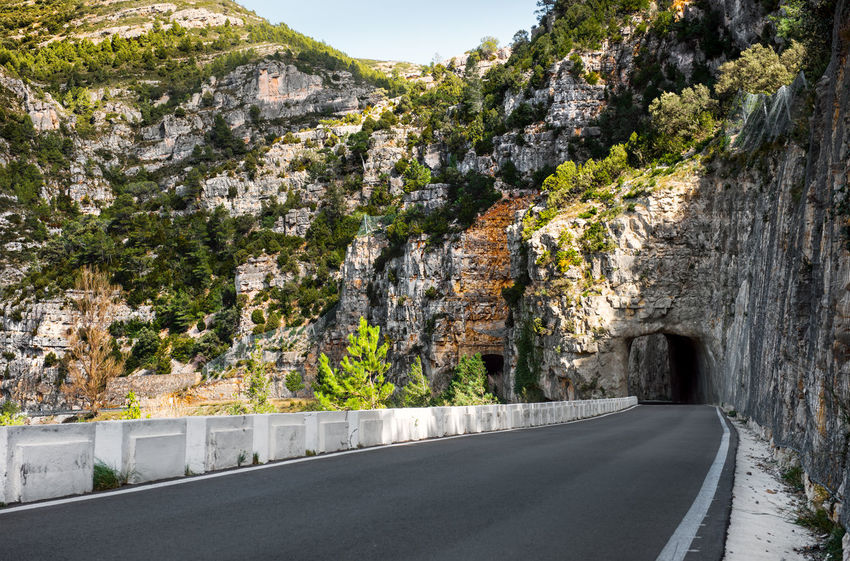 Road along a Ulldecona reservoir. Valencian Community, Spain Asphalt Castellón Catalonia Cliff Dam Day Europe Landscape Nature Nobody Outdoors Reservoir Road Roadside Roadway Rock Formation Rocky Mountains SPAIN Spring Sunny Day Through Travel Destinations Tunnel Ulldecona Way