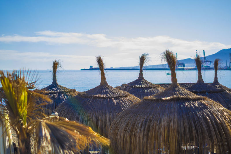 Thatched Roof Sunshades At Beach Against Sky