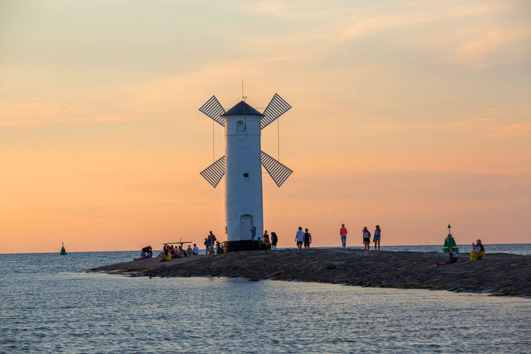 Stawa Młyny Architecture Beauty In Nature Built Structure Group Of People Guidance Horizon Horizon Over Water Incidental People Lighthouse Nature Orange Color Outdoors Real People Scenics - Nature Sea Sky Sunset Tower Water Waterfront