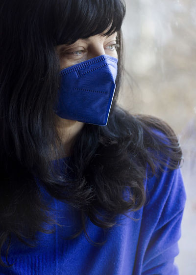 Close-up portrait of woman covering face with blue eyes