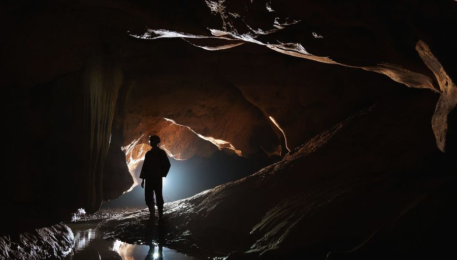 Silhouette man standing in cave