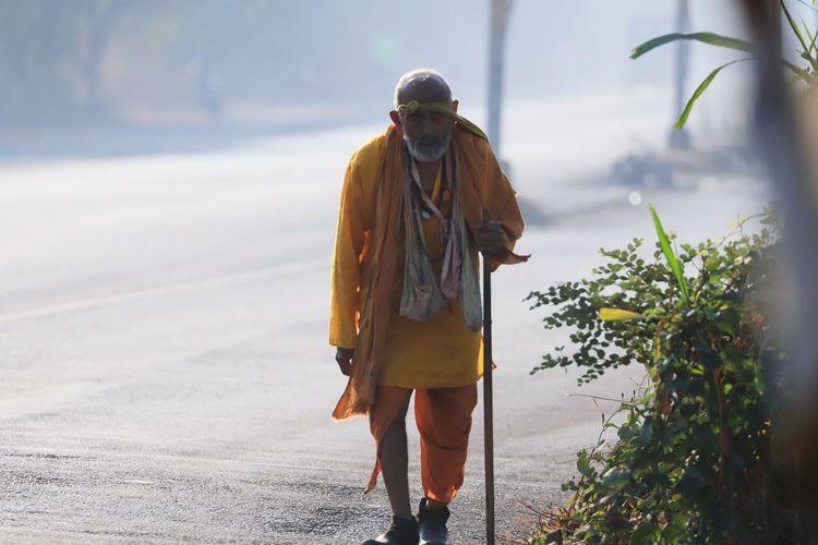 Poor old man walking on the street begging for food.