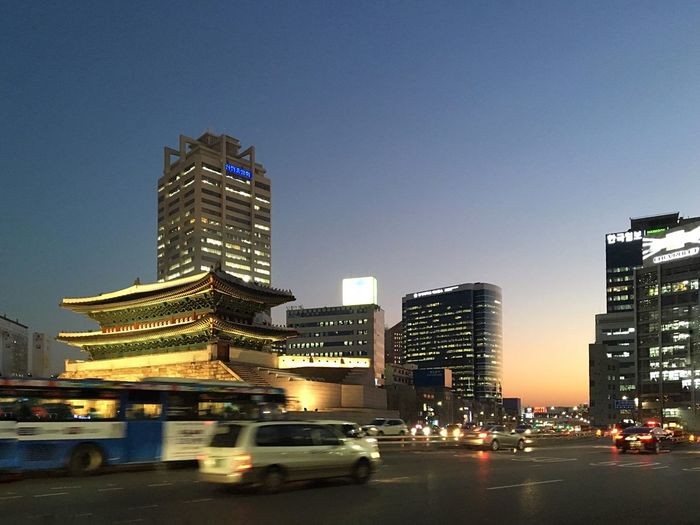 Illuminated namdaemun gate in front of road against clear sky at dusk in city