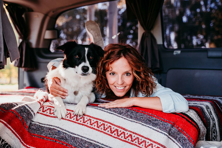 Portrait of woman with dog sitting in car