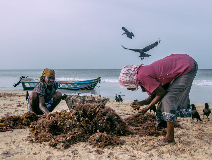 I was walking around the beach when I saw a bunch of fishermen net-fishing and pulling out their catch of the day from the sea. All of these pictures are moments I captured from the scene. My favourite is the one with the man wearing a cap which reads 'Void' and sorts out the fish as crows lurk behind him, hoping to get some of the catch. The Portraitist - 2018 EyeEm Awards Adult Beach Day Fisherman Full Length Horizon Horizon Over Water Land Leisure Activity Lifestyles Men Nature Nautical Vessel People Real People Sea Sky Two People Water