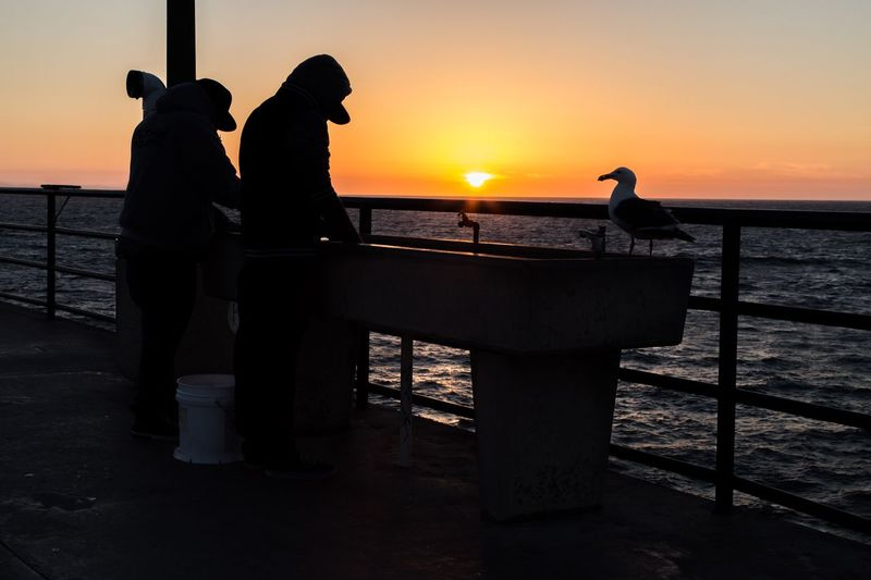 People standing by wash basin against sea during sunset