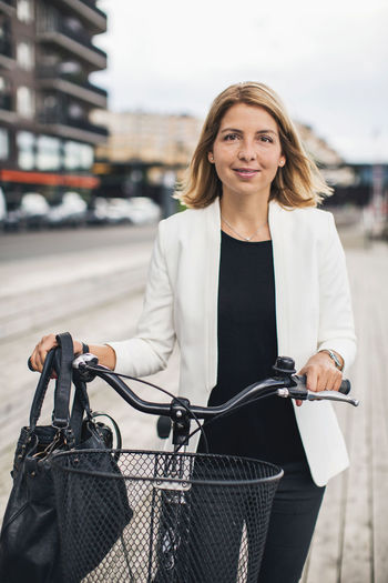 Portrait of smiling woman with bicycle in city